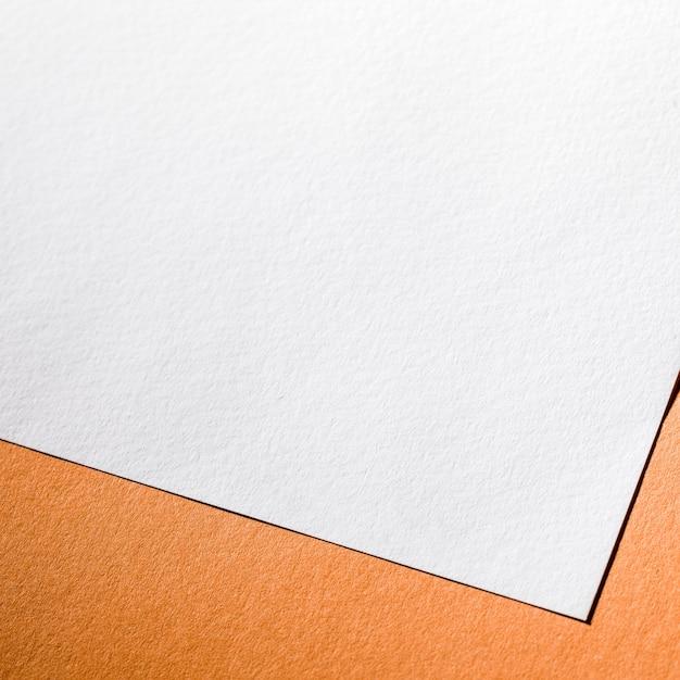 Wit geweven papier op een oranje achtergrond Gratis Foto
