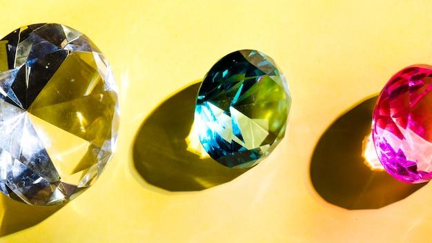 Wit; groene en roze kristaldiamant op gele achtergrond Gratis Foto
