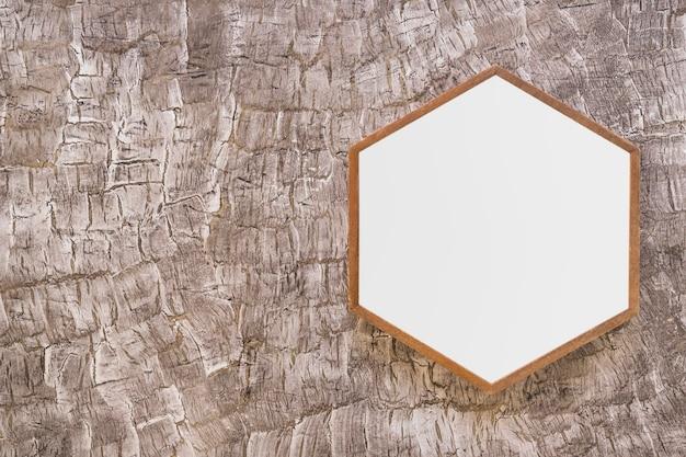 Wit houten hexagon kader op geschilderde muur Gratis Foto