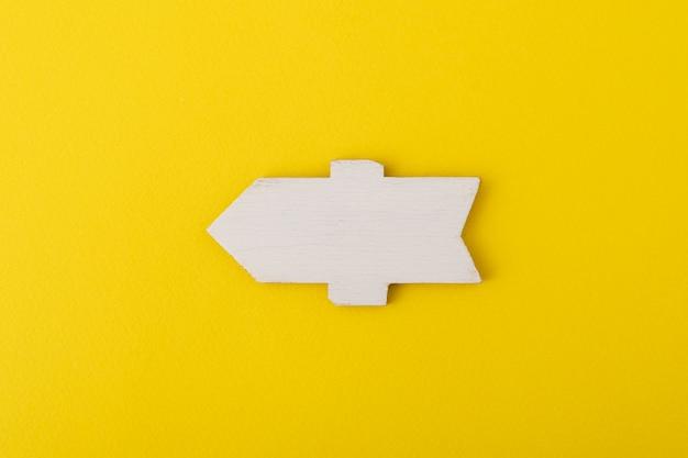 Wit houten richtingsteken op gele achtergrond. Premium Foto