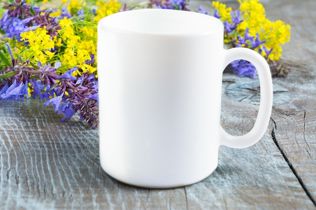 Wit koffiemokmodel met lila en gele bloemen Premium Foto