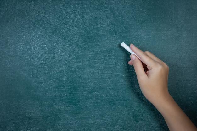 Wit krijt in de hand voor het bord Gratis Foto