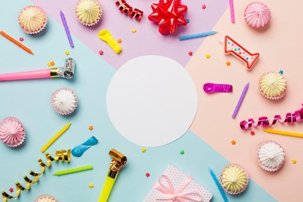 Wit leeg cirkelkader dat met aalaw wordt omringd; hagelslag; streamers; ballon en kaarsen op gekleurde achtergrond Gratis Foto