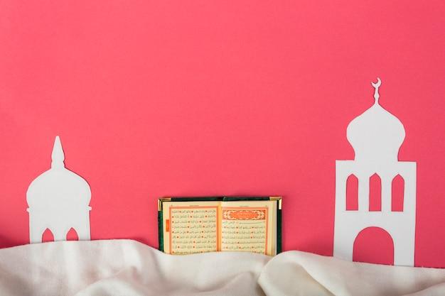 Wit mosquedocument dat met een open heilige islamitische kuran over de rode achtergrond wordt verwijderd Gratis Foto