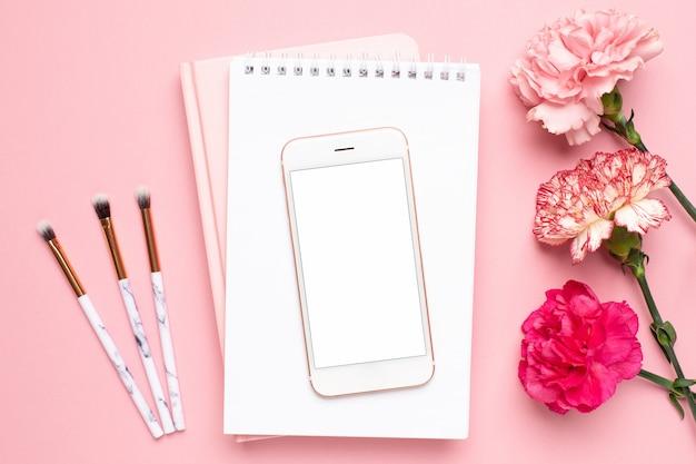 Wit notitieboekje en mobiele telefoon met anjerbloem op een roze achtergrond Premium Foto