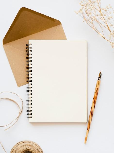 Wit notitieboekje met een houten penpunt op een lichtbruine envelop met een bruine draad en een tak op een witte achtergrond Gratis Foto