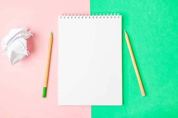 Wit open notitieboekje op groene en roze achtergronden. in de buurt zijn potloden. Premium Foto