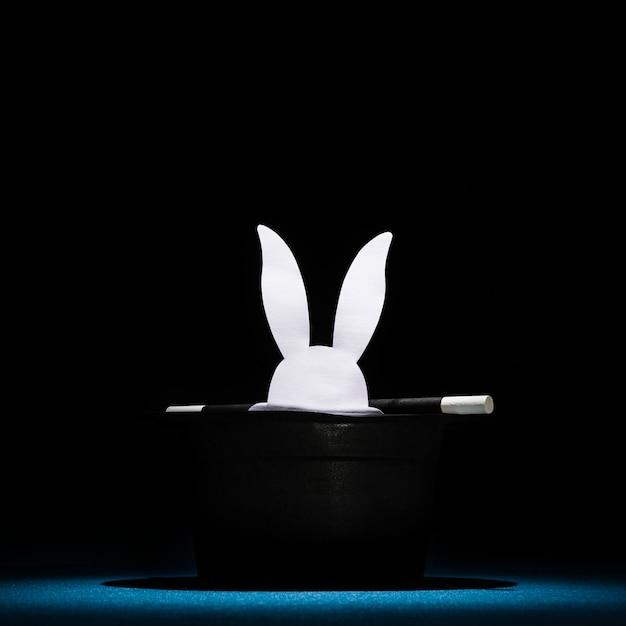 Wit papier sneed konijnenhoofden uit in de bovenste zwarte hoed met toverstaf Gratis Foto