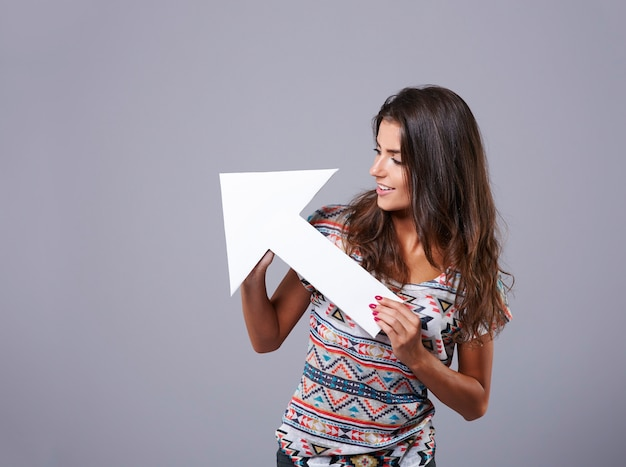 Wit pijlteken dat door aantrekkelijke jonge vrouw wordt gehouden Gratis Foto