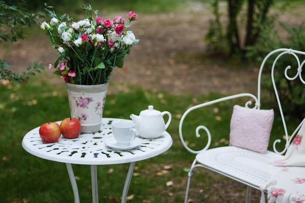 Wit porselein voor thee of koffie op tafel in de tuin over vervagen groene natuur. zomer buiten feest setting. Premium Foto