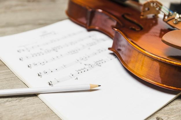 Wit potlood en viool op muzieknoot over de houten achtergrond Gratis Foto