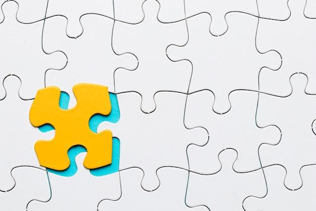 Wit puzzelraster met gele puzzel stuk achtergrond Gratis Foto