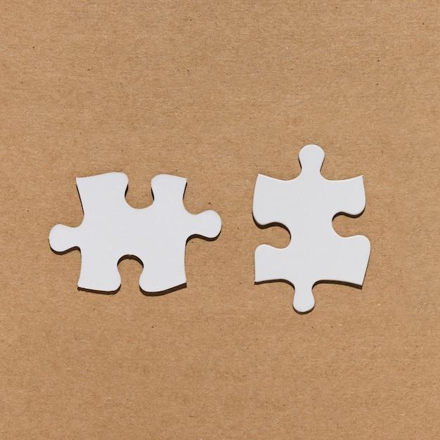 Wit puzzelstuk over pakpapier geweven achtergrond Gratis Foto
