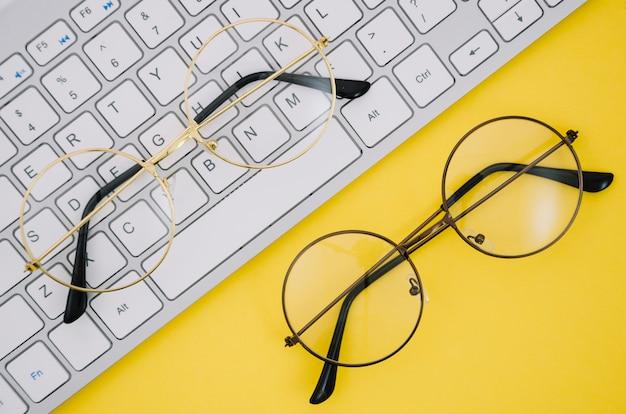 Wit toetsenbord en een bril op gele achtergrond Gratis Foto