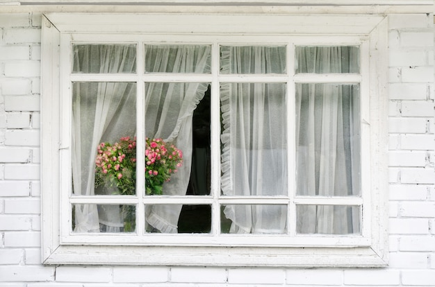 Wit venster met gordijnen, een boeket bloemen op de vensterbank Premium Foto