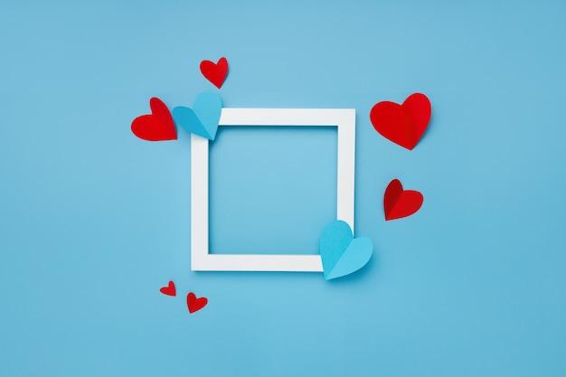 Wit vierkant frame op blauwe achtergrond met papieren harten Gratis Foto