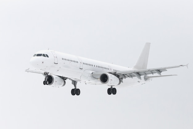 Wit vliegtuig met chassis in de lucht die voor landing voorbereiden Premium Foto