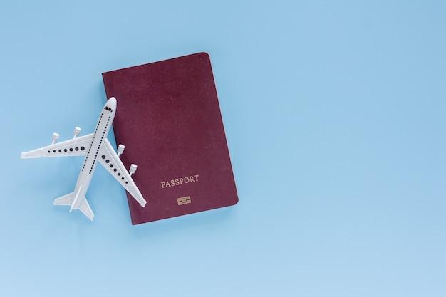 Wit vliegtuigmodel met paspoort op blauw voor reis en reisconcept Premium Foto