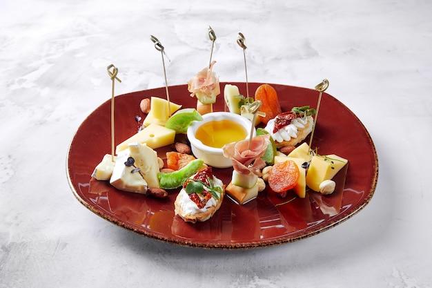 Witbrood tapas met ham en komkommer, met tomatensaus en kaas, liggend op plaat Premium Foto