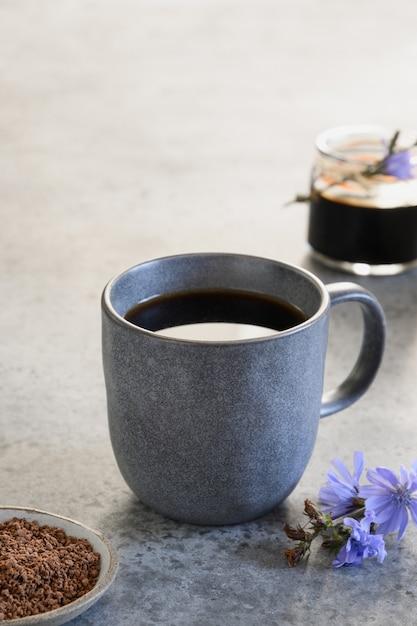 Witlofdrank als koffiesurrogaat in grijze kop en verse bloemen. verticaal formaat. Premium Foto