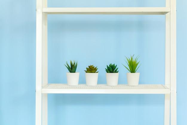 Witmetaalrek met boeken tegen blauwe achtergrond Premium Foto