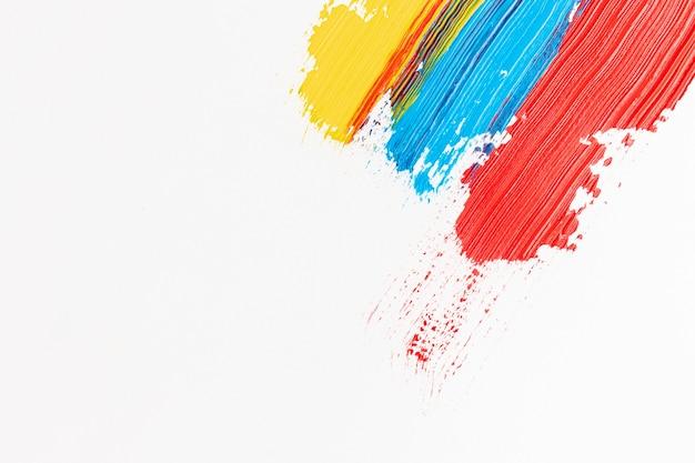 Witte achtergrond met rode, blauwe en gele verf Premium Foto