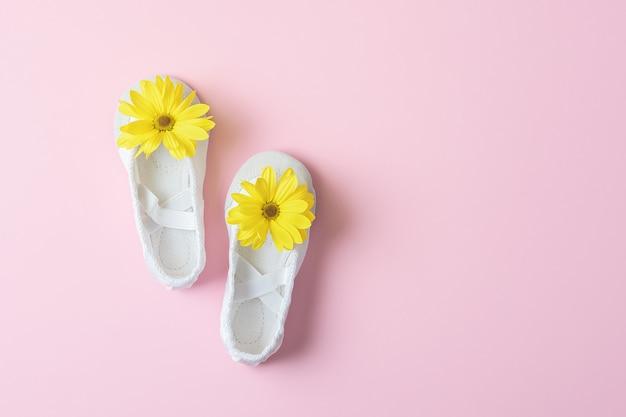 Witte ballerina's met gele bloemen op een roze tafel met kopie ruimte. Premium Foto