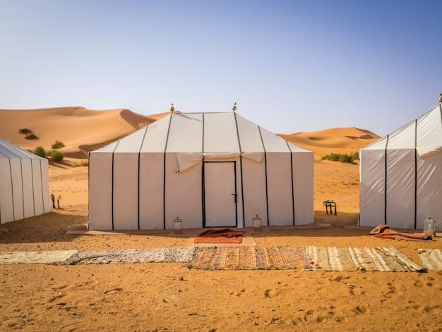 Witte berbertenten in de sahara, marokko met tapijten op de zanderige grond Gratis Foto