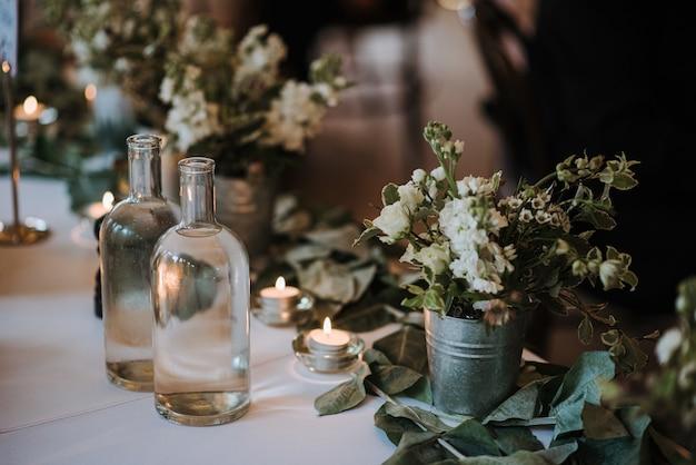 Witte bloemen in een emmer, flessen water en kaarsen op een tafel versierd met bladeren Gratis Foto