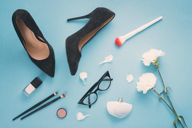 Witte bloemen met cosmetica en vrouwenschoenen op blauwe lijst Gratis Foto