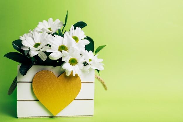 Witte bloemenvaas met hartvorm op groene achtergrond Gratis Foto