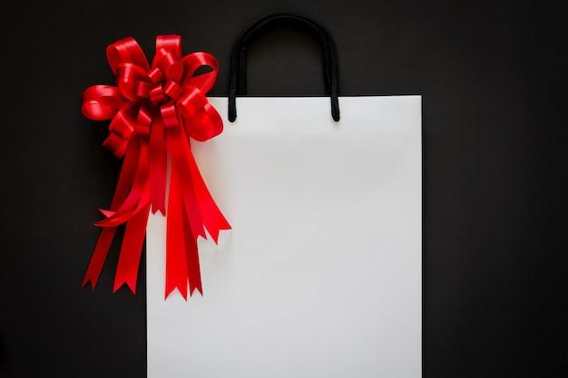 Witte boodschappentas met rode strik en lint op zwart Premium Foto