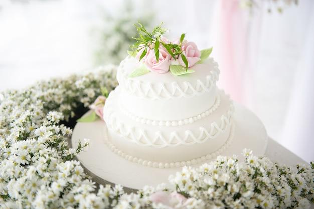 Witte bruidstaart met bloemen en vetplanten bij bruiloft avenue receptie. Premium Foto