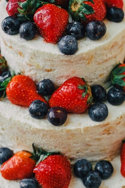 Witte bruidstaart versierd met kersen, aardbeien en bosbessen Premium Foto