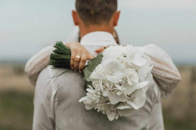 Witte bruiloft boeket gemaakt van callas en een vrouw is buitenshuis een man knuffelen Gratis Foto
