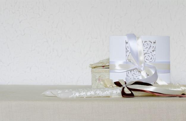 Witte bruiloft uitnodiging op de textuur, kaarsen versierd met linten Premium Foto