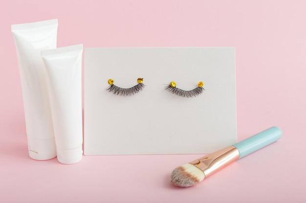 Witte buizen met mock-up voor ontwerp. valse wimpers, make-upborstel op roze achtergrond. Premium Foto