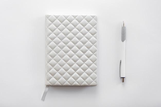 Witte bureau tafel met een notitieboekje en pen erop Gratis Foto