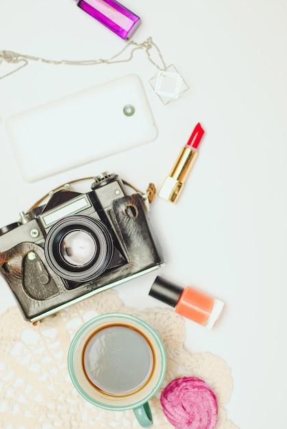 Witte bureaulijst met smartphone, uitstekende camera, koffie en schoonheidsmiddelen. Premium Foto