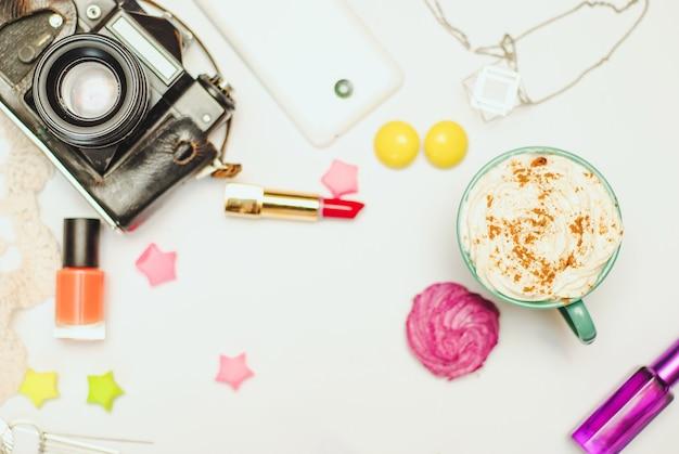 Witte bureaulijst met smartphone, uitstekende camera, kruid latte en schoonheidsmiddelen. Premium Foto