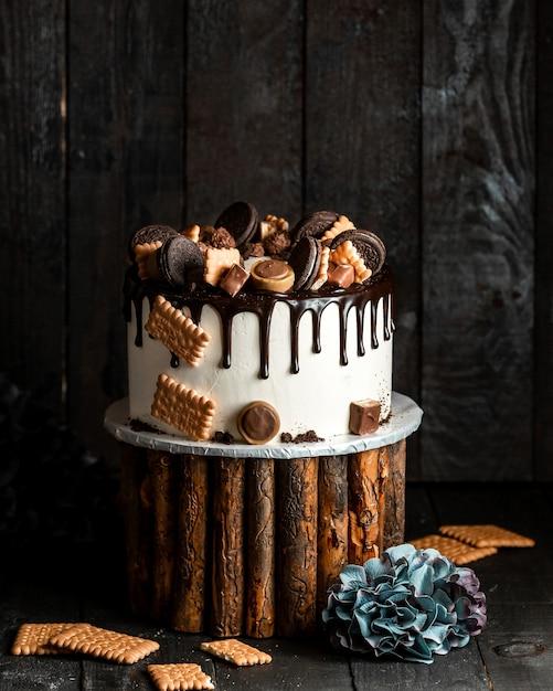 Witte cake gegoten met chocolade en versierd met verschillende koekjes Gratis Foto