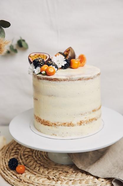 Witte cake met bessen en passievruchten met planten Gratis Foto