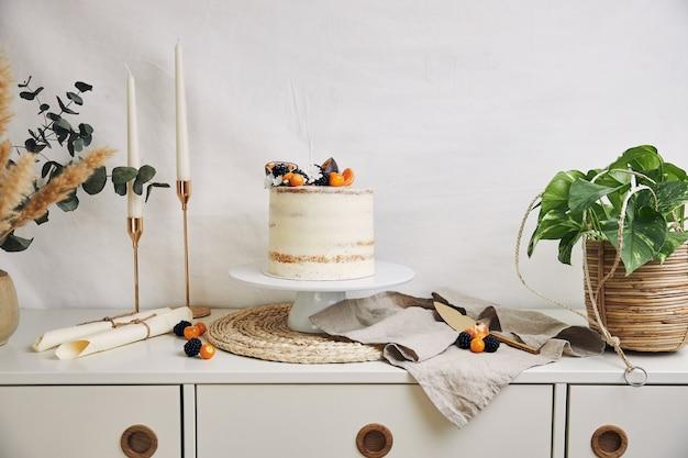 Witte cake met bessen en passievruchten naast planten en kaarsen op wit Gratis Foto