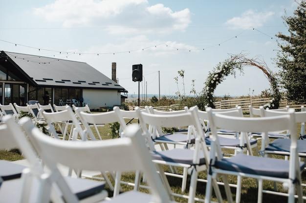 Witte chiavari stoelen voor gasten, ceremoniële huwelijksboog op de versierde voor de huwelijksceremonie Gratis Foto