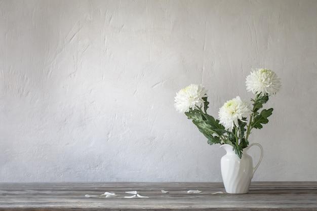 Witte chrysant in kruik op oude muur als achtergrond Premium Foto