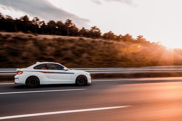 Witte coupé sedan rijden op de weg in de zonsondergang Gratis Foto
