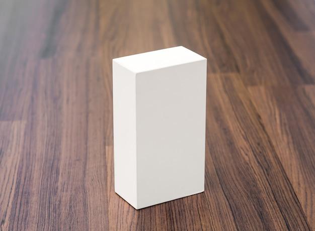 Witte doos op houten tafel Gratis Foto
