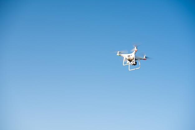 Witte drone vliegt in de lucht en neemt een video op Gratis Foto