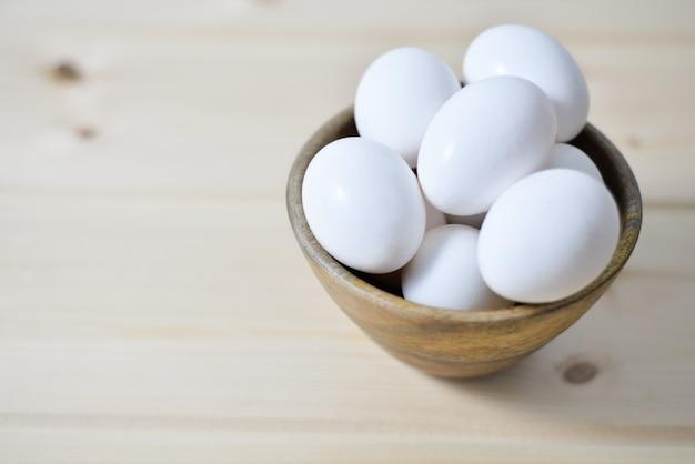 Witte eieren ןמ houten plaat op houten achtergrond Premium Foto
