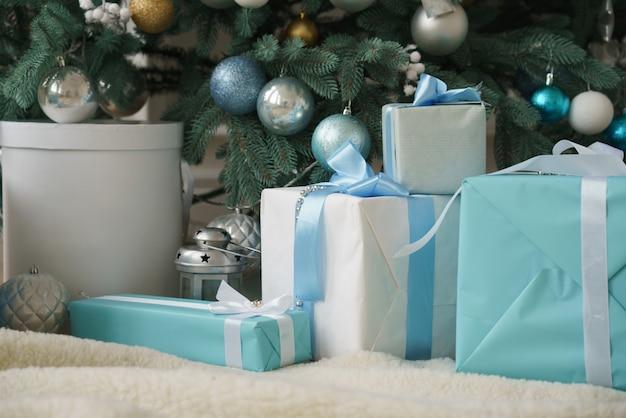 Witte en blauwe geschenkdozen met blauwe linten onder gedecoreerde kerstboom Premium Foto